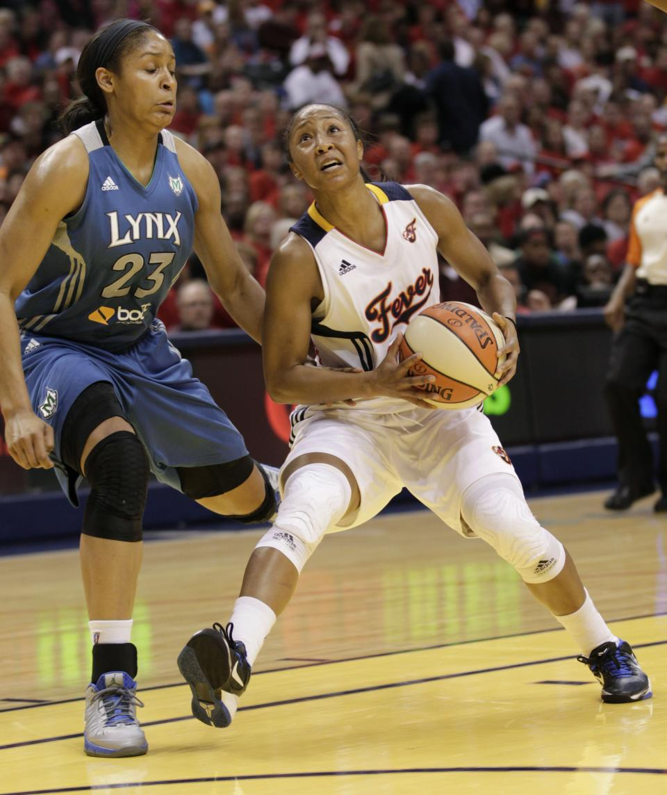 Indiana Fever guard Briann January, right, goes to the basket in front of Minnesota Lynx forward Maya Moore (23) in the first half of Game 3 of the WNBA basketball Finals, Friday, Oct. 19, 2012, in Indianapolis. (AP Photo/AJ Mast)