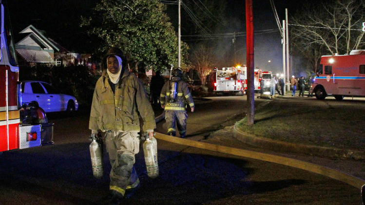 A fireman carries empty oxygen tanks from battling a fire in a west Jackson, Miss., home where authorities say a small plane carrying three people crashed shortly after 5 p.m. Tuesday evening, Nov. 13, 2012. The home's resident is believed to have escaped but authorities have not released names of plane's passengers.  (AP Photo/Rogelio V. Solis)