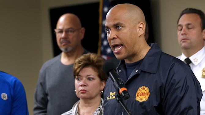 FILE - In this Oct. 29, 2012, file photo, Newark Mayor Cory Booker, right, speaks during a news conference at the Office of Emergency Management in Newark, N.J. Booker says he plans to honor a Twitter challenge and live on food stamps for at least a week. In a Twitter exchange Sunday, Nov. 18, 2012, Booker and a user named TwitWit discussed government funding for school meals. Booker suggested they both try living on food stamps for a week or month. (AP Photo/Julio Cortez, File)