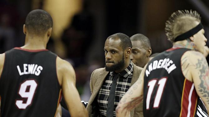 Miami Heat's LeBron James, center, congratulates his teammates after a 96-95 win over the Cleveland Cavaliers in an NBA basketball game Monday, April 15, 2013, in Cleveland. James sat out the game. (AP Photo/Mark Duncan)