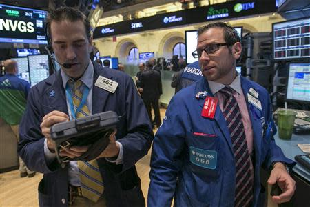 Specialist trader Michael Pistillo gives a price to trader Greg Rowe on the floor of the New York Stock Exchange