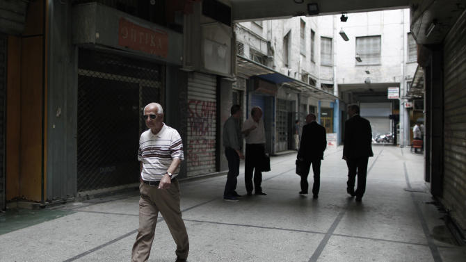 People walk past shuttered shops in a rundown commercial arcade in central Athens on Friday, June 7, 2013. Greece's statistical authority on Friday revised its first quarter recession figures, saying the economy contracted by 5.6 percent in January-March instead of the initially-estimated 5.3 percent. Debt-crippled Greece is in its sixth year of recession, and is surviving on international bailouts issued in return for stringent austerity measures that have led to record-high unemployment. (AP Photo/Petros Giannakouris)