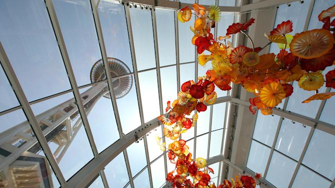 """FILE - In this May 17, 2012 photo, the Space Needle is seen through the walls and ceiling of the """"Glasshouse,"""" featuring a 100-foot suspended, 1,340-piece sculpture, during a preview of the Chihuly Garden and Glass exhibit at the Seattle Center in Seattle.   Fifty years after the World's Fair inserted the Space Needle into Seattle's skyline, the city is celebrating that anniversary by offering an array of new things to see and do at Seattle Center: from a zip line to the new art glass museum.  (AP Photo/Elaine Thompson)"""