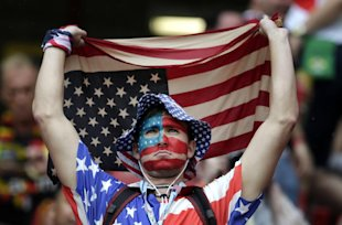 A US fan holds a flag prior to the group G World Cup soccer match between the USA and Germany at the Arena Pernambuco in Recife, Brazil, Thursday, Jun...