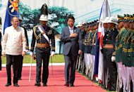 Japan's Prime Minister Shinzo Abe (C-R) and Philippine President Benigno Aquino (L) review an honour guard during Abe's welcoming ceremony at the Malacanang Palace in Manila, on July 27, 2103. Abe is in Manila for a two-day visit focusing on defence cooperation amid territorial disputes with China