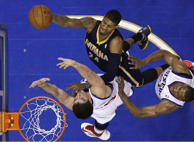 Indiana Pacers' Paul George, center, goes up for a shot against Philadelphia 76ers' Byron Mullens, left, and Thaddeus Young during the second half of an NBA basketball game, Friday, March 14,