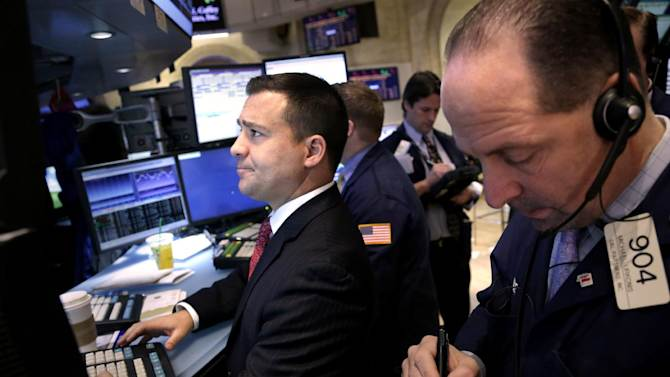 "Traders work on the floor at the New York Stock Exchange in New York, Monday, Dec. 31, 2012.  The stock market struggled for direction Monday morning after five days of losses, with the ""fiscal cliff"" just hours away and lawmakers yet to reach a solution. (AP Photo/Seth Wenig)"