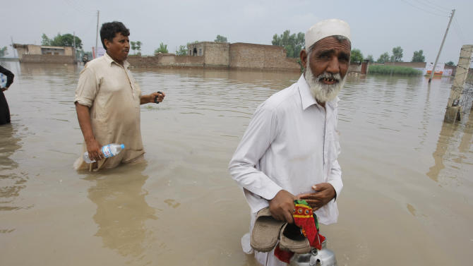 Pakistani flood victims wade through floodwater to reach their homes in Peshawar, Pakistan, Monday, Aug. 3, 2015. Pakistani authorities said the death toll from flash floods triggered by seasonal monsoon rains in various parts of the country has risen to more than 100. Meanwhile, floodwater has inundated vast areas, leaving tens of thousands homeless. (AP Photo/Mohammad Sajjad)
