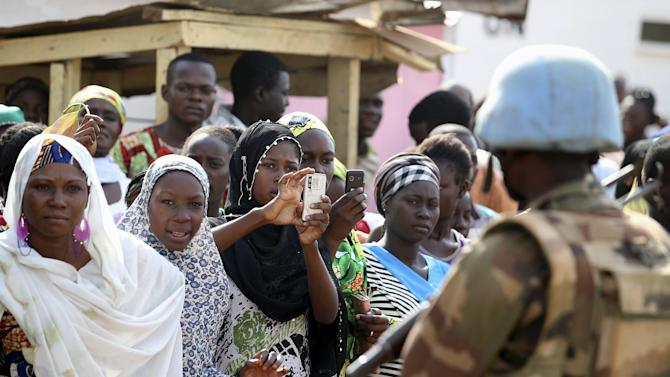 A woman takes a picture of a United Nations peacekeeper near the Koudoukou Mosque in Bangui, Central African Republic