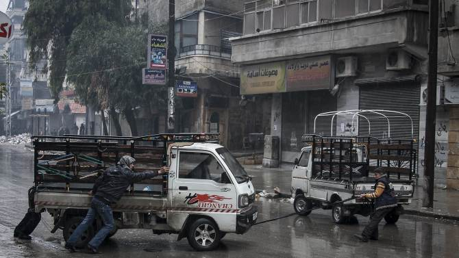 In this Friday, Dec. 07, 2012 photo, Syrian residents pull a  truck that has run out of gas on  a street in the Sukari district of Aleppo, Syria. Residents must cope with a shortage of fuel and supplies and rainy winter weather as they try to continue with their daily life. (AP Photo/Narciso Contreras)