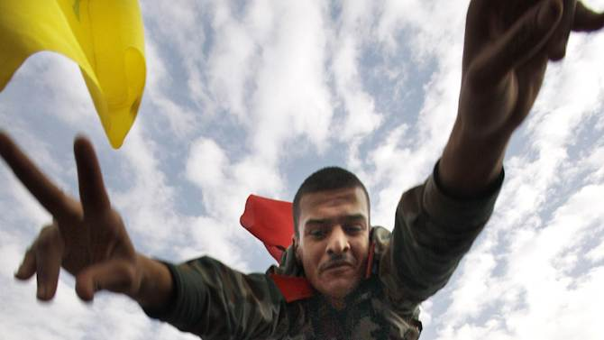 FILE - A Syrian solider flashes the victory sign as he is thrown in the air during a rally at Umayyad Square in Damascus, Syria, Wednesday, Dec. 21, 2011. (AP Photo/ Muzaffar Salman, File)