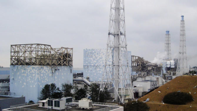 In this image released by Tokyo Electric Power Co., smoke billows from the No. 3 unit among four housings cover four reactors at the Fukushima Dai-ichi nuclear complex in Okumamachi, Fukushima Prefecture, northeastern Japan, on Tuesday, March 15, 2011. Japan ordered emergency workers to withdraw from its stricken nuclear complex Wednesday amid a surge in radiation, temporarily suspending efforts to cool the overheating reactors. Hours later, officials said they were preparing to send the team back in. (AP Photo/Tokyo Electric Power Co.) EDITORIAL USE ONLY