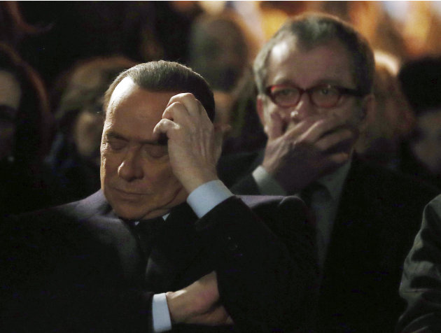 Former Italian Premier Silvio Berlusconi, foreground, sits in front of Norther League party's leader Roberto Maroni in Milan, Italy, Sunday, Jan. 27, 2013. Silvio Berlusconi says Benito Mussolini did