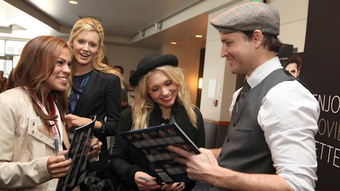 Toni Trucks, Maggie Grace and MyAnna Buring, from left to right, get an autograph from Peter Facinelli at the Time Warner Cable and Twilight Fan Breakfast on Sunday, Nov. 11, 2012 in Los Angeles. (Photo by Casey Rodgers/Invision for Time Warner Cable/AP Images)