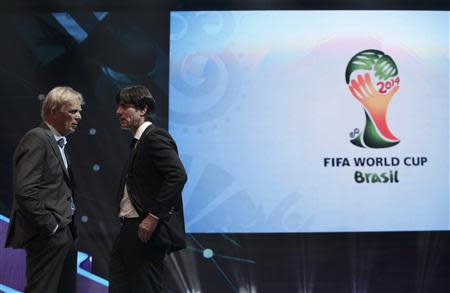 Low talks to Finke during the draw for the 2014 World Cup in Sao Joao da Mata