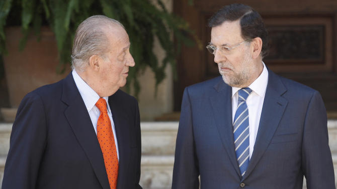 Spain's King Juan Carlos, left, speaks with Spanish Prime Minister Mariano Rajoy before their meeting at the Marivent Palace in Palma de Mallorca, Spain, Tuesday, Aug. 14, 2012. Rajoy said Tuesday he had still not made a decision on asking for more financial aid for his country and would not until the European Central bank made known plans and conditions for for buying troubled government bonds. (AP Photo/Manu Mielniezuk)