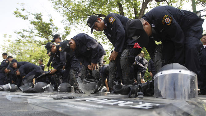 Thai policemen put on their gears before patrol outside Government House in Bangkok, Friday, Nov. 23, 2012. Anti-government protesters are expected to show up in Bangkok on Saturday to demand an overthrow of the current government under the rule of Prime Minister Yingluck Shinawatra. (AP Photo/Sakchai Lalit)
