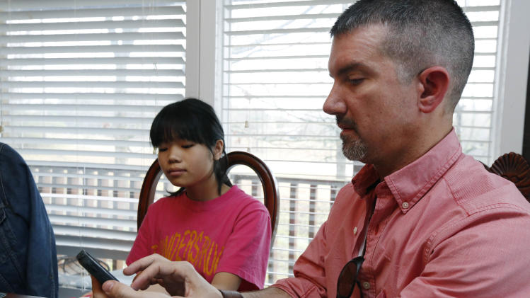 "In this April 4, 2013 photograph, Phillip Smith uses Google Translate to ""speak"" with his new daughter, 14-year-old Guan Ya, in their Rienzi, Miss., home. Smith, his wife Niki Smith and their three other children are using the program to communicate almost exclusively with Guan Ya, who is deaf. The family uses iPhones, iPods and a laptop, all loaded with the program to write in either English that translates to Chinese or vice-a-versa. (AP Photo/Rogelio V. Solis)"
