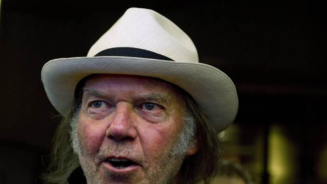 """FILE - In a Monday, Sept., 12, 2011 file photo, musician Neil Young arrives for the film """"Neil Young Journeys"""" at the Toronto International Film Festival in Toronto. The organizers of the annual publishing convention, BookExpo America announded Monday, March 19, 2012 that Young will speak June 6, 2012, about his upcoming memoir, """"Waging Heavy Peace,"""" scheduled to come out this fall. (AP Photo/The Canadian Press, Nathan Denette, File)"""