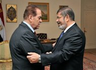 Egypt's president-elect Mohamed Morsi (right) shake hands with prime minister-elect Kamal al-Ganzuri in his new offices in the Al-Ittihadiya presidential palace in Cairo. Morsi is drawing up a battle plan to confront Egypt's economic and security crises as he pushed ahead with selecting a government of technocrats, a senior aide told AFP
