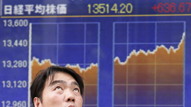 A man looks up by the day's chart of Tokyo's Nikkei 225, the regional heavyweight, that soared 636.67 points, or 4.94 percent, to 13,514.20 in front of a securities firm in Tokyo Monday, June 10, 2013. Asian markets rose Monday after U.S. jobs data helped allay concern the Fed might wind down its stimulus and Japan's prime minister promised new tax cuts. (AP Photo/Koji Sasahara)