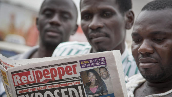 """A Ugandan reads a copy of the """"Red Pepper"""" tabloid newspaper in Kampala, Uganda Tuesday, Feb. 25, 2014. The Ugandan newspaper published a list Tuesday of what it called the country's """"200 top"""" homosexuals, outing some Ugandans who previously had not identified themselves as gay, one day after the president Yoweri Museveni enacted a harsh anti-gay law. (AP Photo/Rebecca Vassie)"""