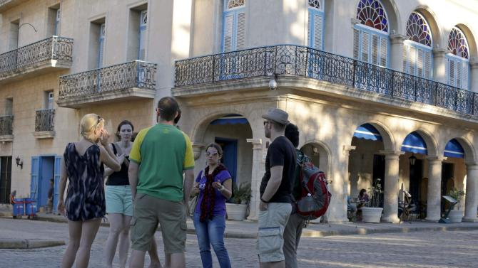 Tourists talk with a guide near a hotel in Old Havana