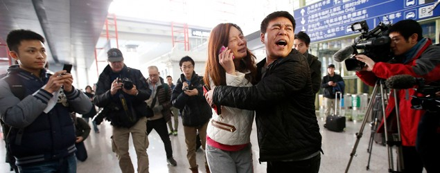 A woman (C), believed to be the relative of a passenger onboard Malaysia Airlines flight MH370, cries as she talks on her mobile phone at the Beijing Capital International Airport in Beijing, March 8, 2014. (REUTERS/Kim Kyung-Hoon)