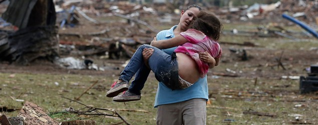 A woman carries her child through a field near the collapsed Plaza Towers Elementary School in Moore, Okla. (Sue Ogrocki/AP)