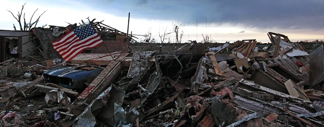 An American flag blows in the wind at sunrise atop the rubble of a destroyed home a day after a tornado moved through Moore, Okla. (Brennan Linsley/AP)