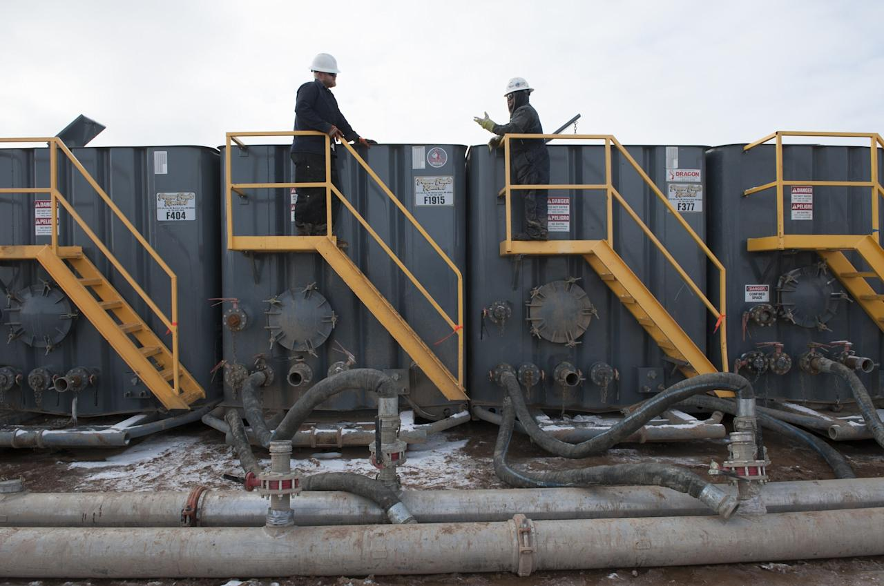 Workers monitor water tanks at a Hess fracking site near Williston, North Dakota November 12, 2014. Falling oil prices have yet to spoil North Dakota's party, with billions of investment dollars still flowing for new wells and pipelines, apartments and shopping centers, a tacit bet the third energy boom in the state's history is just getting started. Picture taken November 12, 2014.  REUTERS/Andrew Cullen  (UNITED STATES - Tags: BUSINESS COMMODITIES ENERGY)