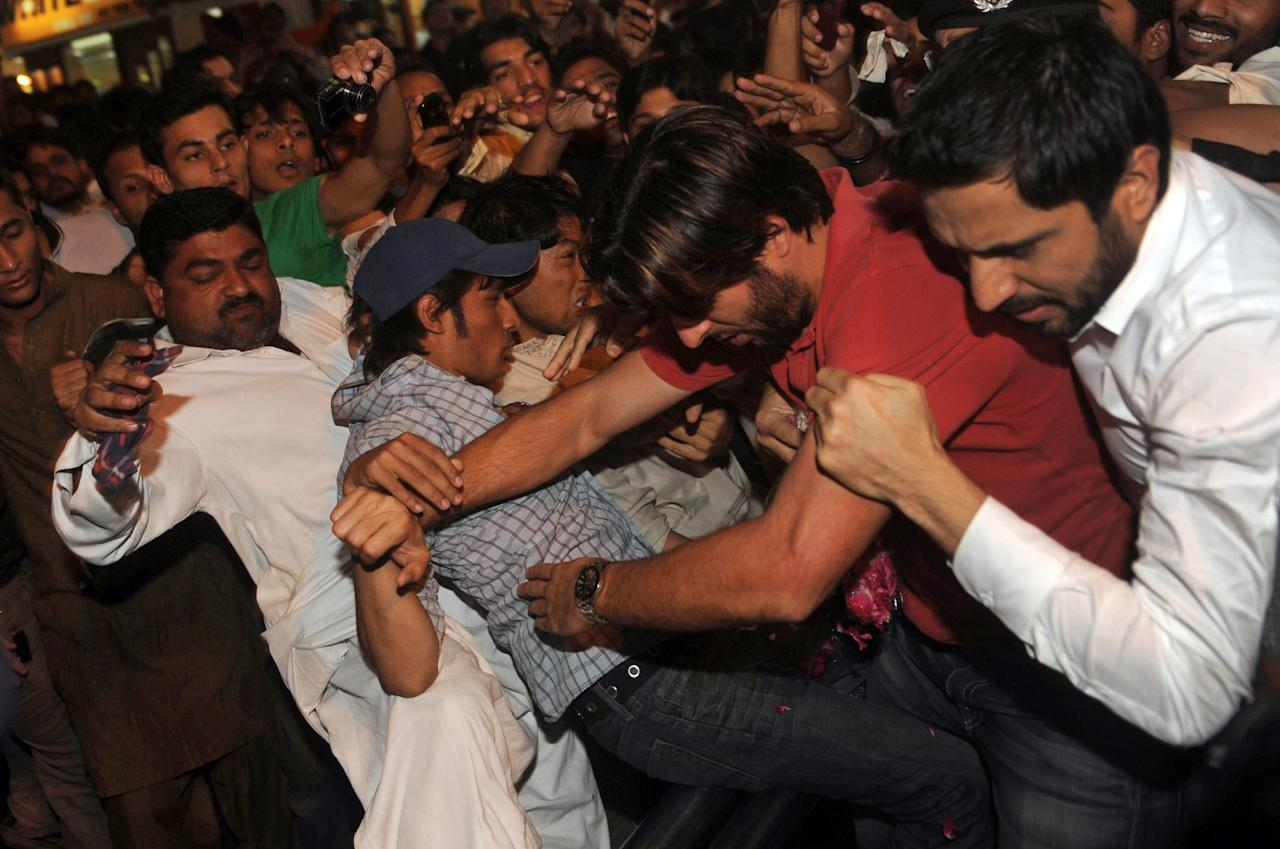 Pakistan cricketer Shahid Afridi (2nd R) pushes his way past fans at the airport following his return to Karachi late on March 23, 2012. Pakistan allrounder Shahid Afridi lashed out at fans at Karachi airport after his three-year-old daughter was hurt in a crush of autograph hunters, eye-witnesses and television reports said March 23. The 32-year-old former captain lost his temper and hit fans who had descended on the airport to greet members of the Asia Cup winning national side, apparently after his daughter Ajwa was hurt.  AFP PHOTO/Rizwan TABASSUM (Photo credit should read RIZWAN TABASSUM/AFP/Getty Images)