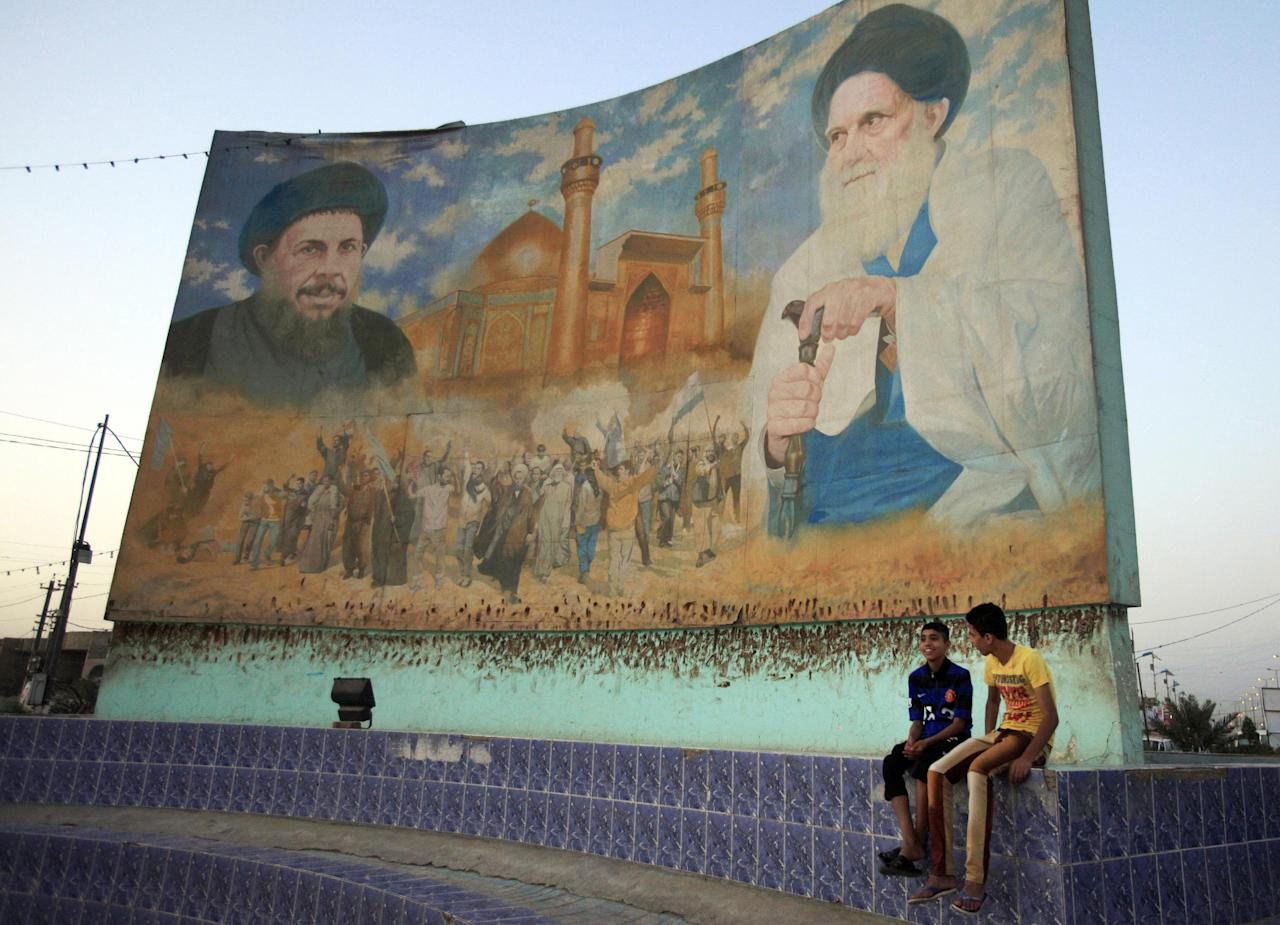 In this Saturday, April 6, 2013 photo, Iraqi boys sit next to a mural that used to be painted with the portrait of former dictator Saddam Hussein, which turned into a mural of Shiite clerics Ayatollah Mohammed Baqir al-Sadr, left, and Grand Ayatollah Mohammed Sadiq al-Sadr, right, in Baghdad, Iraq. Ten years ago, a statue fell in Paradise Square. Joyful Iraqis helped by a U.S. Army tank retriever pulled down their longtime dictator, cast as 16 feet of bronze. The scene broadcast live worldwide became an icon for a war, a symbol of final victory over Saddam Hussein. But for the people of Baghdad, it was only the beginning. The toppling of the statue on April 9, 2003, remains a potent symbol that has divided Iraqis ever since. (AP Photo/ Karim Kadim)