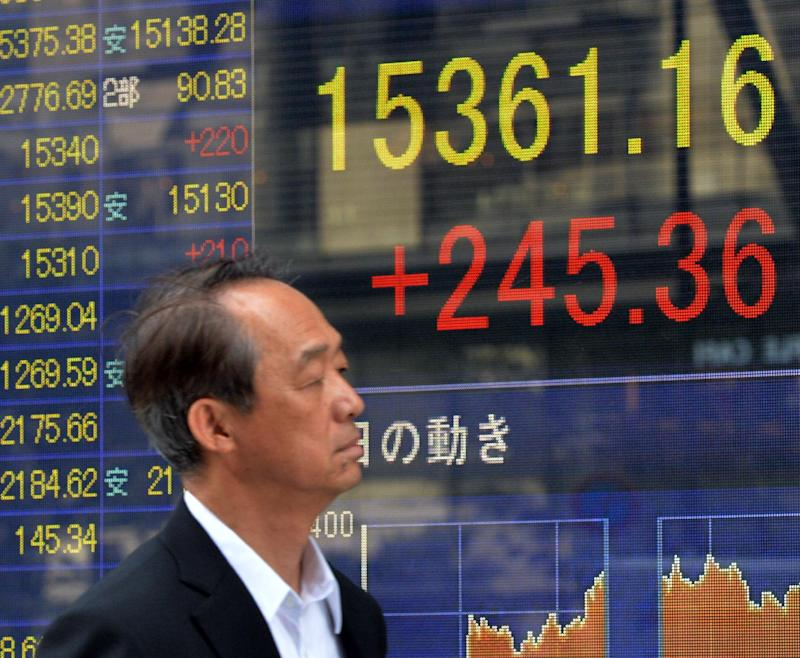 A businessman passes before a share prices board in Tokyo on June 19, 2014