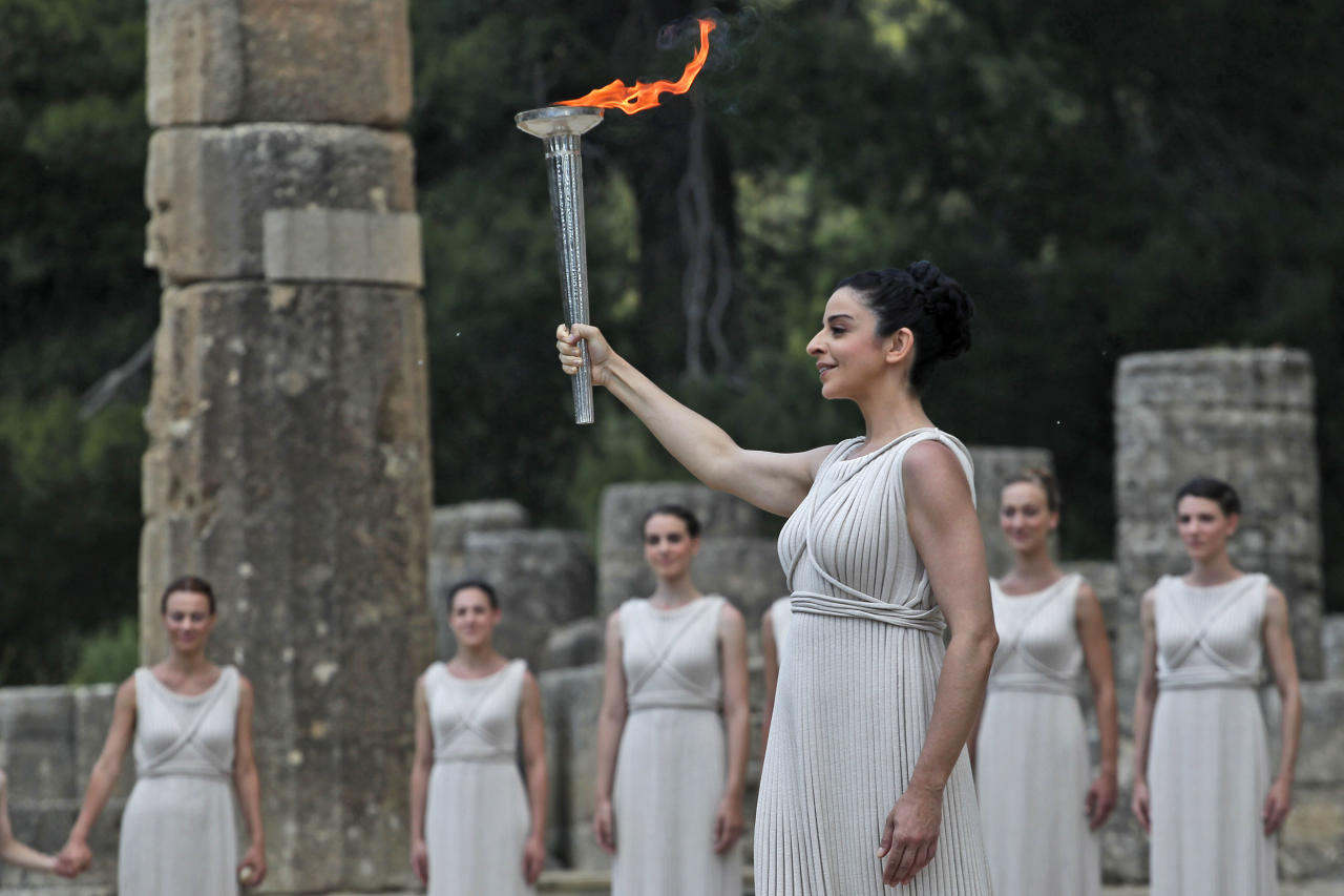 An actress as a high priestess, holds up a torch with the Olympic flame she has just lit using a concave mirror to concentrate the sun's rays during the lighting of the flame ceremony, on Thursday May 10, 2012, in Ancient Olympia, Greece. The flame, lit in the birthplace of the Ancient Olympics, will travel to London, where the Summer Games will take place from July 27-Aug. 12. (AP Photo/Petros Giannakouris)