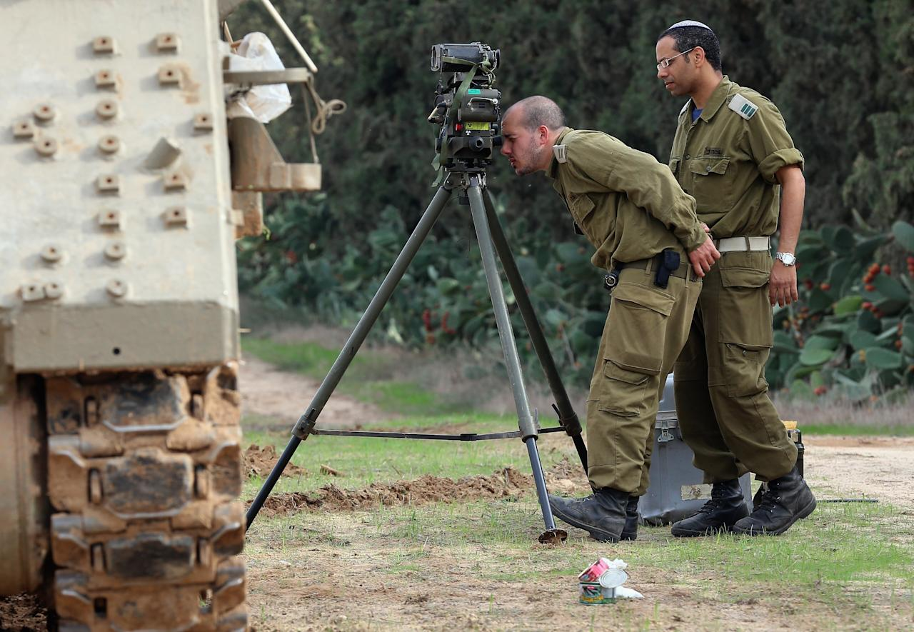 ISRAEL/GAZA BORDER, ISRAEL- NOVEMBER 19:  Israeli soldiers prepare an artillery emplacement overlooking Gaza on November 19, 2012 on Israel's border with the Gaza Strip. The death toll has risen to at least 85 killed in the air strikes, according to hospital officials, on day six since the launch of operation 'Pillar of Defence.'  (Photo by Christopher Furlong/Getty Images)