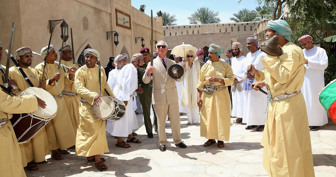 NIZWA, OMAN - MARCH 18:  Prince Charles, Prince of Wales performs a traditional sword dance with local Omanis as Camilla, Duchess of Cornwall looks on as they visit Nizwa Fort on the eighth day of a tour of the Middle East on March 18, 2013 in Nizwa, Oman. The Royal couple are on the fourth and final leg of a tour of the Middle East taking in Jordan, Qatar, Saudia Arabia and Oman.  (Photo by Chris Jackson/Getty Images)