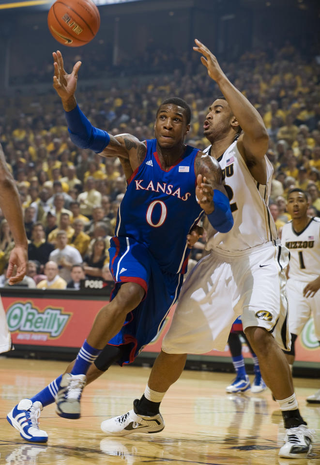 Kansas' Thomas Robinson, left, loses control of the ball as Missouri's Steve Moore, right, defends during the first half of an NCAA college basketball game on Saturday, Feb. 4, 2012, in Columbia, Mo. (AP Photo/L.G. Patterson)