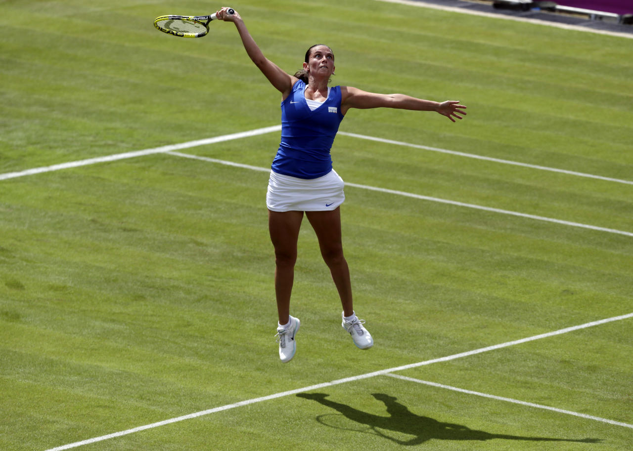 Roberta Vinci of Italy jumps to return to Kim Cljisters of Belgium in a first round tennis match at the All England Lawn Tennis Club in Wimbledon, London at the 2012 Summer Olympics, Saturday, July 28, 2012. (AP Photo/Elise Amendola)