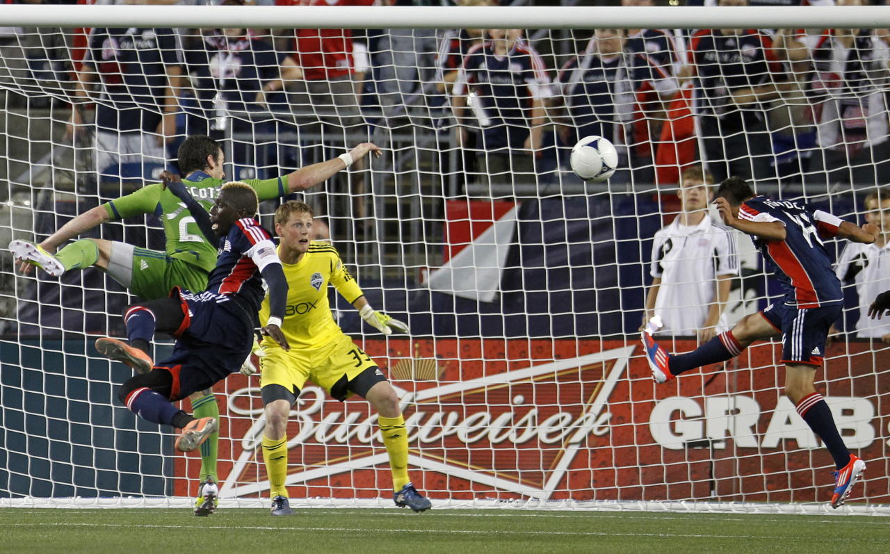 New England Revolution's Diego Fagundez, right, heads the ball into the net past Seattle Sounders' Bryan Meredith (35) in the second half of an MLS soccer game in Foxborough, Mass., Saturday, June 30, 2012. The teams tied 2-2. (AP Photo/Michael Dwyer)