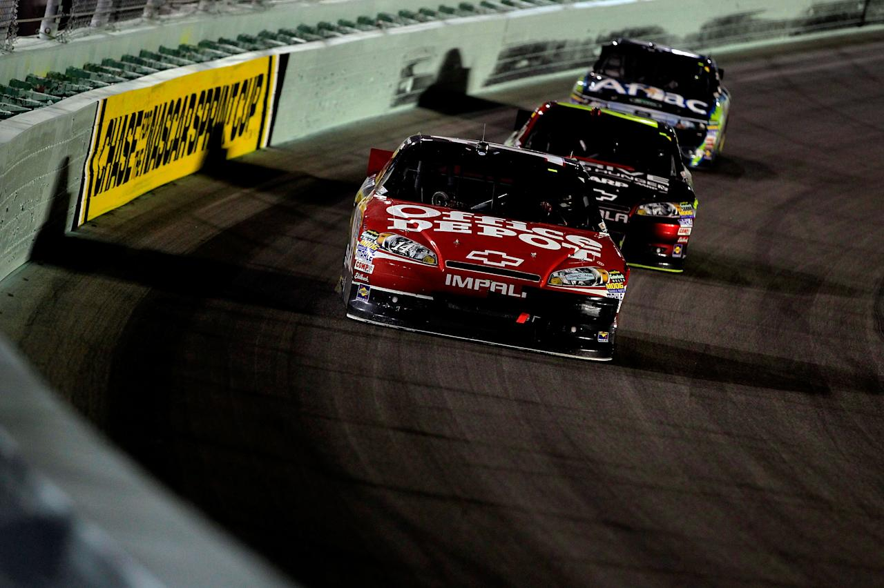 HOMESTEAD, FL - NOVEMBER 20:  Tony Stewart, driver of the #14 Office Depot/Mobil 1 Chevrolet, leads Jeff Gordon, driver of the #24 Drive to End Hunger Chevrolet, and Carl Edwards, driver of the #99 Aflac Ford, during the NASCAR Sprint Cup Series Ford 400 at Homestead-Miami Speedway on November 20, 2011 in Homestead, Florida.  (Photo by Chris Trotman/Getty Images for NASCAR)