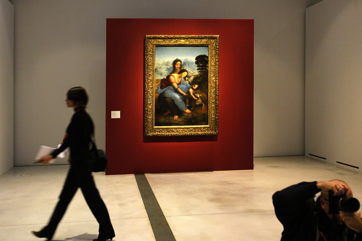 "A woman walk past ""La Vierge, l'Enfant Jesus et Sainte Anne"" by Leonard de Vinci in the Louvre Museum in Lens."
