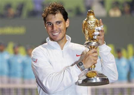 Nadal of Spain holds his trophy after winning the Qatar Open final tennis match in Doha