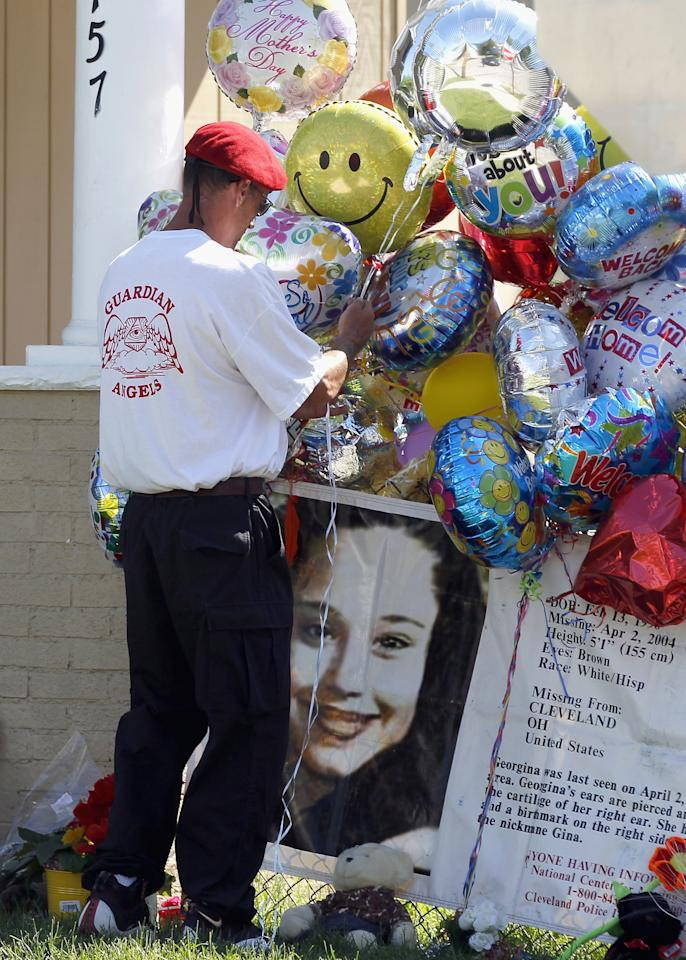 CLEVELAND, OH - MAY 09:  A member of the Guardian Angels ties balloons outside the home of kidnap victim Gina DeJesus on May 9, 2013 in Cleveland, Ohio.  Ariel Castro was arraigned on rape and kidnapping charges for abducting DeJesus, Michelle Knight and Amanda Berry and holding them for about 10 years. No charges were filed against Ariel's brothers, Onil or Pedro and they were released by the judge. Bail was set at $8 million for Ariel. (Photo by Matt Sullivan/Getty Images)