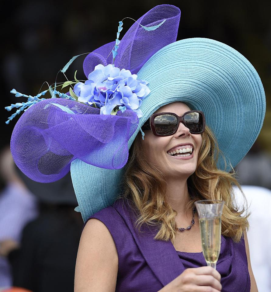 Stephanie Rohrer, of Alexandria Va., speaks with friends during horse racing before the 139th Preakness Stakes horse race at Pimlico Race Course, Saturday, May 17, 2014, in Baltimore. (AP Photo/Nick Wass)