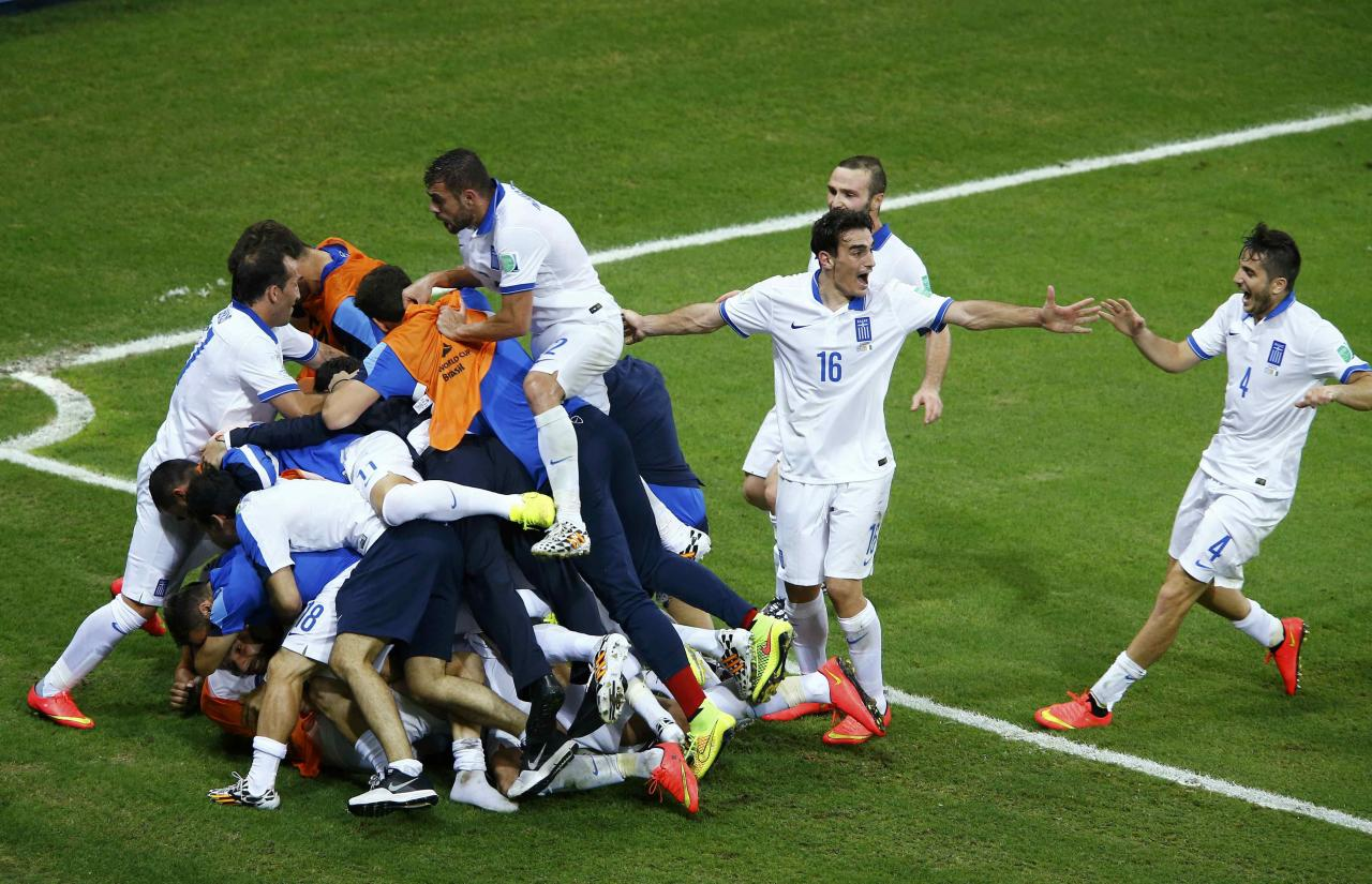 Greece's Giorgios Samaras (obscured) is surrounded by teammates as they celebrate his penalty goal against Ivory Coast during their 2014 World Cup Group C soccer match at the Castelao arena in Fortaleza June 24, 2014. REUTERS/Mike Blake (BRAZIL - Tags: SOCCER SPORT TPX IMAGES OF THE DAY WORLD CUP)