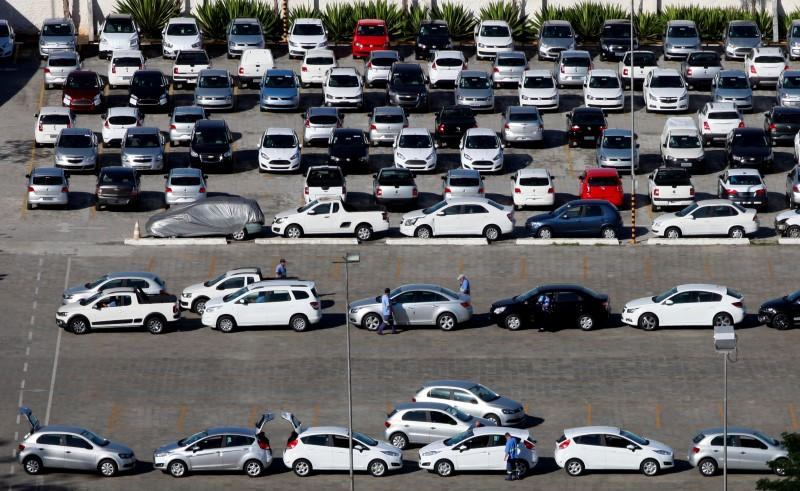 Workers check new cars before they are transported to dealers in Sao Bernardo do Campo