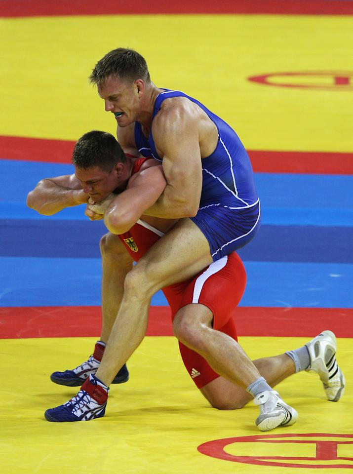 BEIJING - AUGUST 14:  Adam Wheeler (blue) of the USA gets to grips with Mirko Englich (red) of Germany in the Men's Greco-Roman 96kg semi final bout at the China Agriculture University Gymnasium during Day 6 of the Beijing 2008 Olympic Games on August 14, 2008 in Beijing, China.  (Photo by Ezra Shaw/Getty Images)