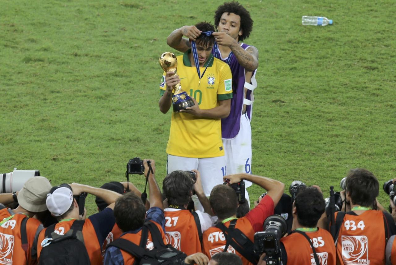 Brazil's Neymar holds the champions trophy as teammate Marcelo places a medal over his head after they defeated Spain in the Confederations Cup final soccer match at the Estadio Maracana in Rio de Janeiro June 30, 2013. REUTERS/Paulo Whitaker (BRAZIL - Tags: SPORT SOCCER)