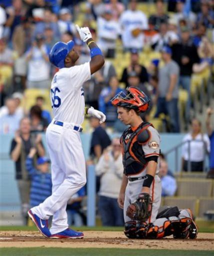 Los Angeles Dodgers' Yasiel Puig, left, points to the sky after hitting a solo home run as San Francisco Giants catcher Buster Posey kneels during the first inning of their baseball game, Monday, June 24, 2013, in Los Angeles. (AP Photo/Mark J. Terrill)